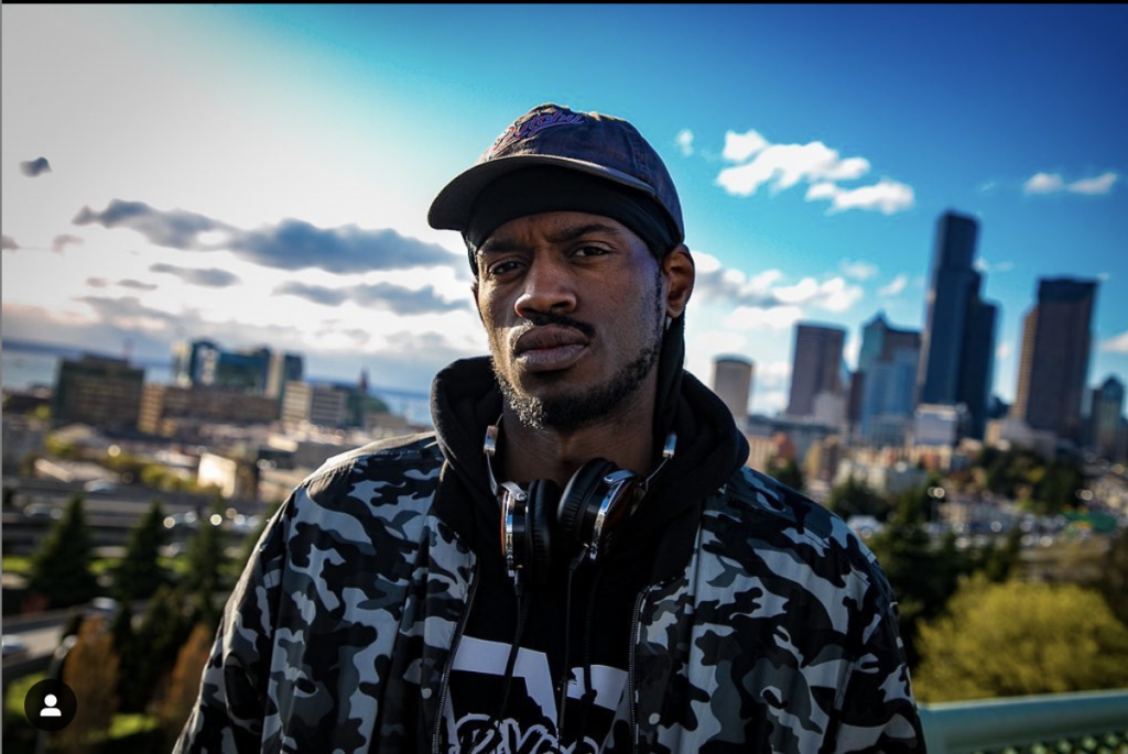 Blake Anthony wears a set of headphones while standing on a hill with the Seattle skyline in the background against a beautiful blue sky.