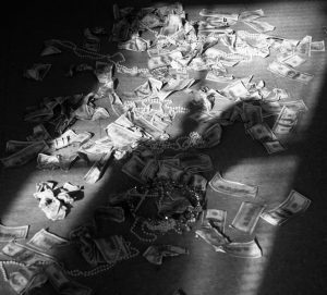 A shadow of a figure standing in a window is seen over a pile of scattered cash and jewelry.