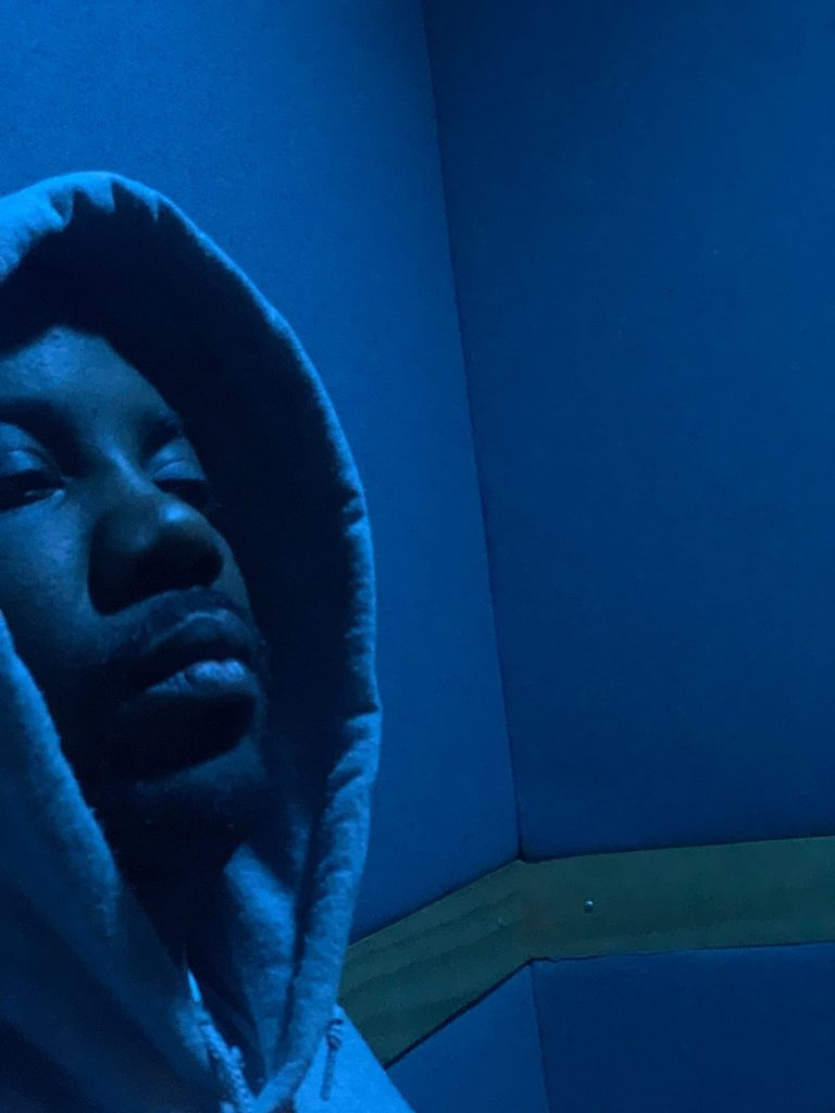 Ace Loner stands in a blue tinted room wearing a hoodie.