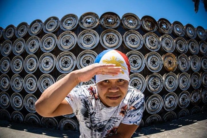 Marlon D salutes while standing outside in front of a stack of wheels.