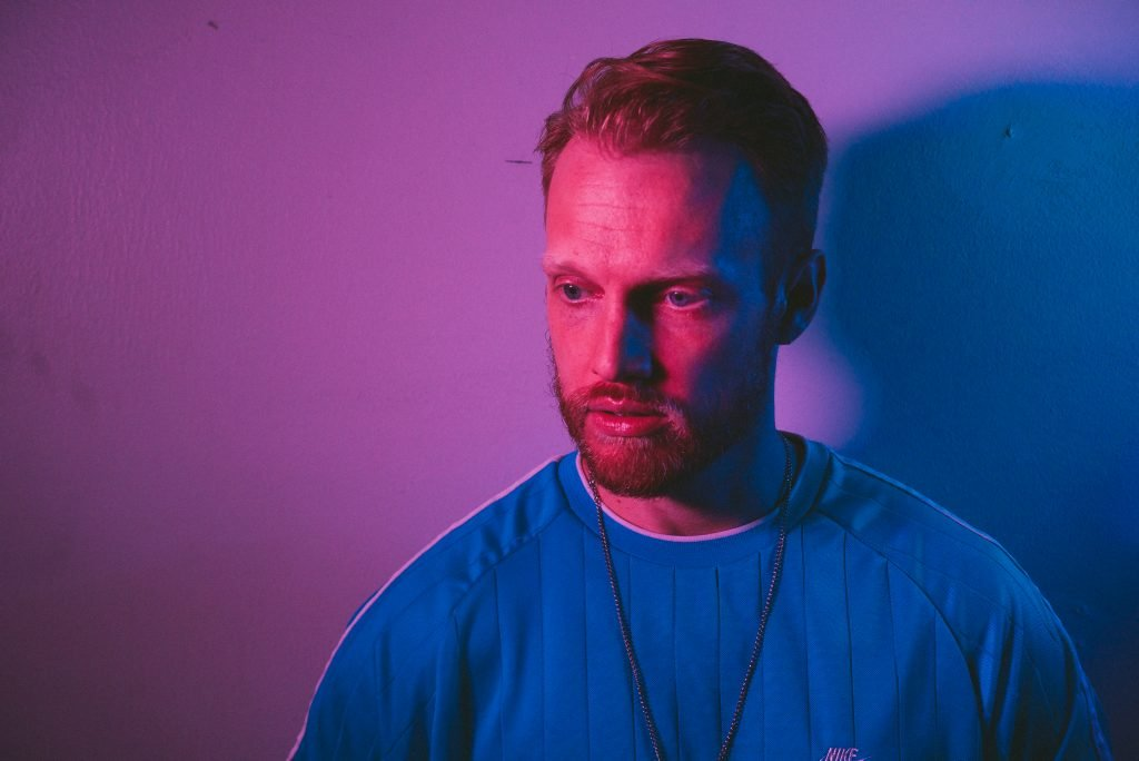 Nick Weaver is set against a purplish backdrop, looking down and thinking.