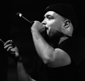 illmac holds a mic in a black and white pic.