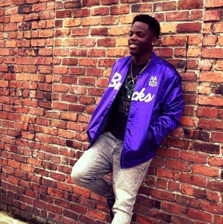 """""""Final Notice"""" is the new project from Jus. Here he is seen wearing a purple satin jacket leaning up against a brick wall."""