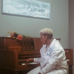"""Livt's new single is """"Sade Til Infinity"""" and here she is seen dressed in all white and playing a piano."""