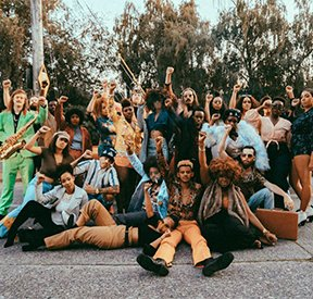 """""""Louder"""" is the new single from Marshall Law Band and Nobi. In this promo image the group is surrounded by a large group of friends."""