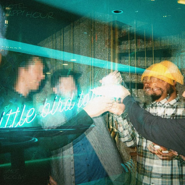 The cover for Myke Bogan's Hotel Happy Hour is a blurry shot of four friends holding up glasses for a toast.