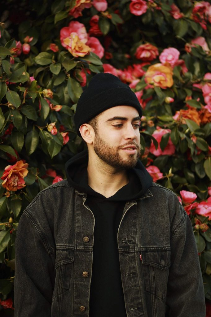 """""""Corduroy"""" is the latest album from Sam Lachow. Here he is pictured standing in front of some flowers in a black beanie, hoodie, and jean jacket while smiling and looking to his left."""