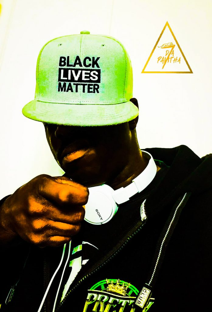 Seven Da Pantha wears a lime green Black Lives Matter hat and a black hoodie while pointing a gun gesture at the viewer.