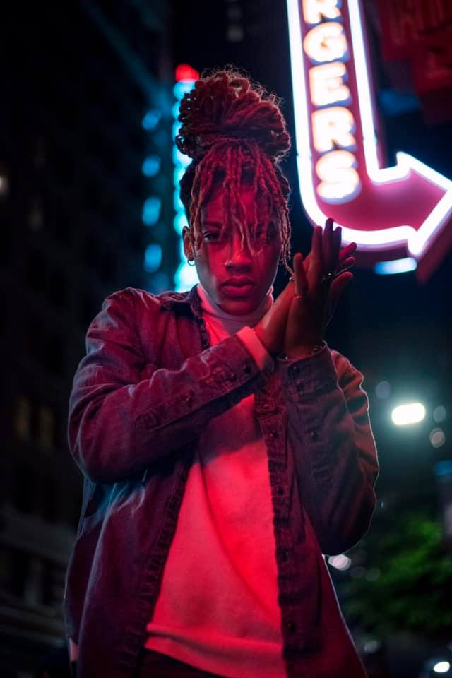 Insane is the new single from Yel. Here you can see her standing with her hands against each other while standing outside under a neon bar sign.