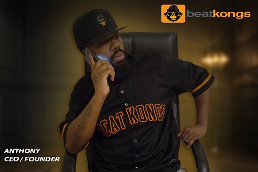 BeatKongs.com founder Anthony Bass wears an orange and black Beat Kongs jersey while sitting and talking on his cell phone.