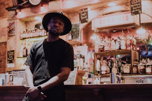 Ayo is dressed in a black t shirt and dark, circular-brimmed hat while leaning against a bar.