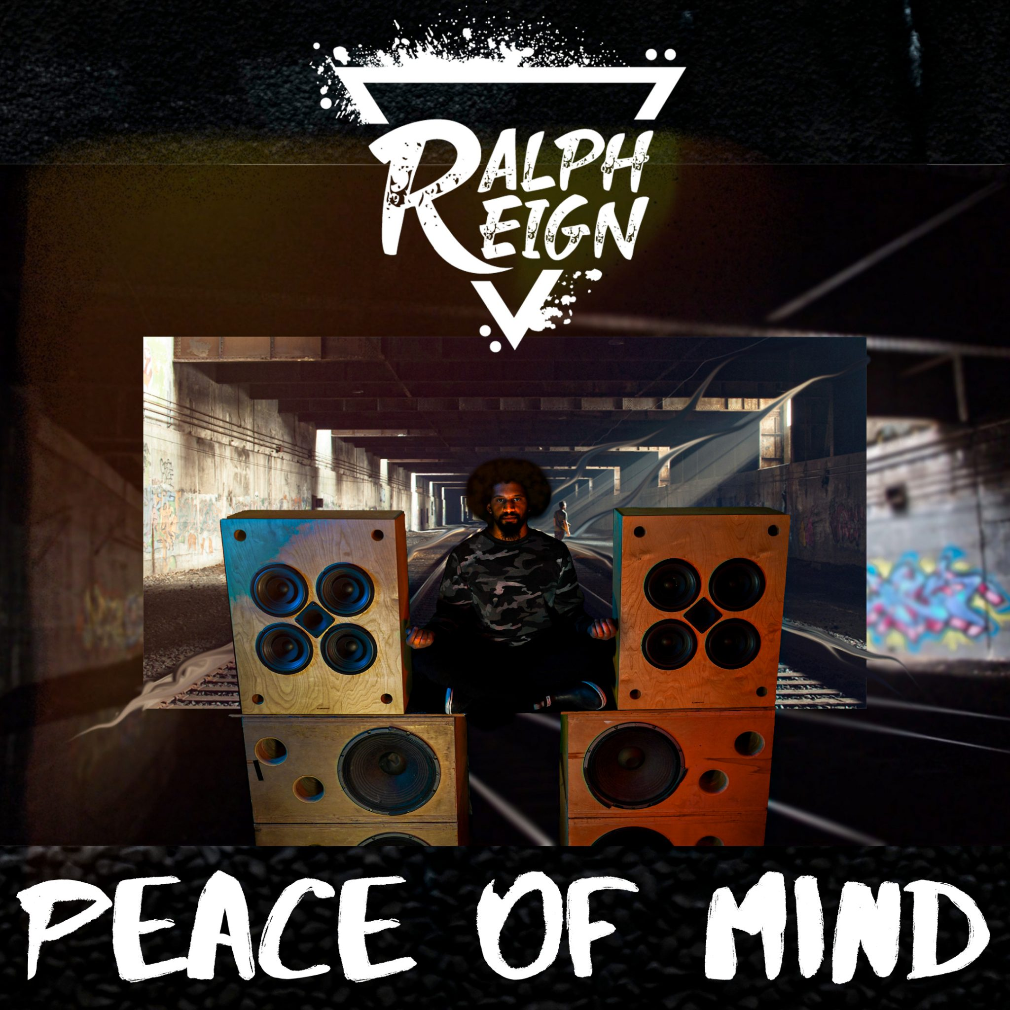 """On the cover for his single """"Peace of Mind"""", Ralph Reign stands with his arms outstretched between two speaker towers."""