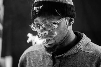 Real Kozby blows smoke out in a black and white image.