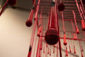 Red microphones hang from ceiling.