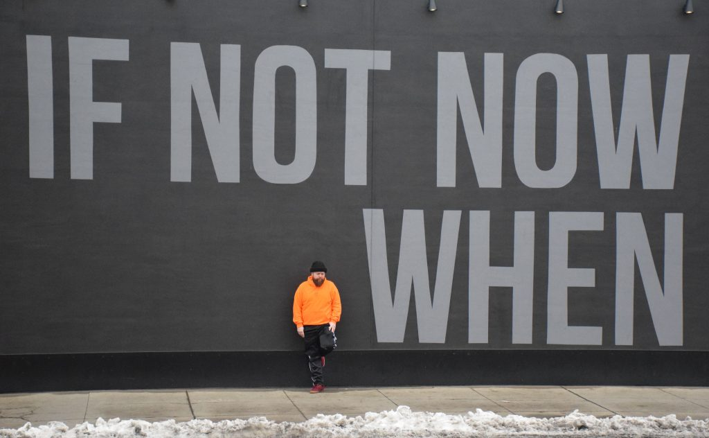 """Barz! stands in front a black wall with the words """"If Not Now When"""" painted in gray on it."""