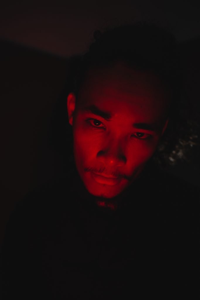 Closeup image of Nobi's face with a red light on it and the background very dark.