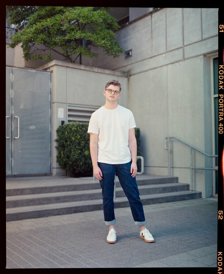 Hunter Gillam is seen here standing in a white t-shirt and blue jeans.