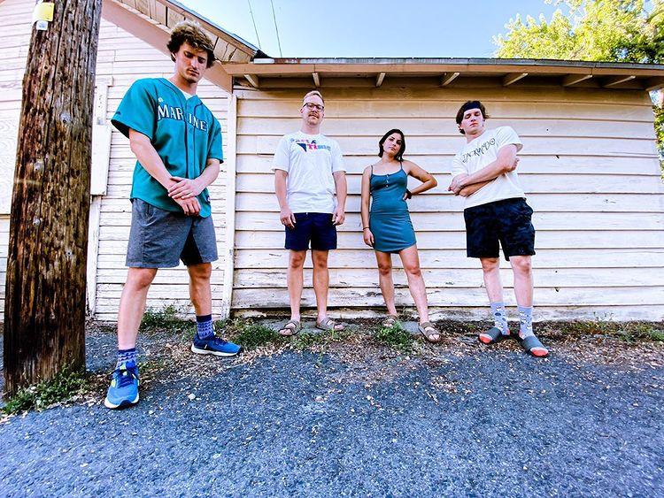 The four members of Jacklando stand outside by a house during the day.