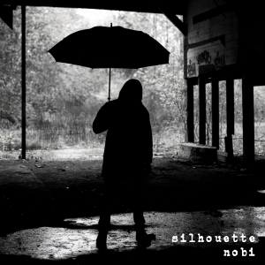 """Cover for Nobi EP """"Silhouette"""" features a shadowy image of Nobi holding an umbrella while standing under an open walled structure outside."""