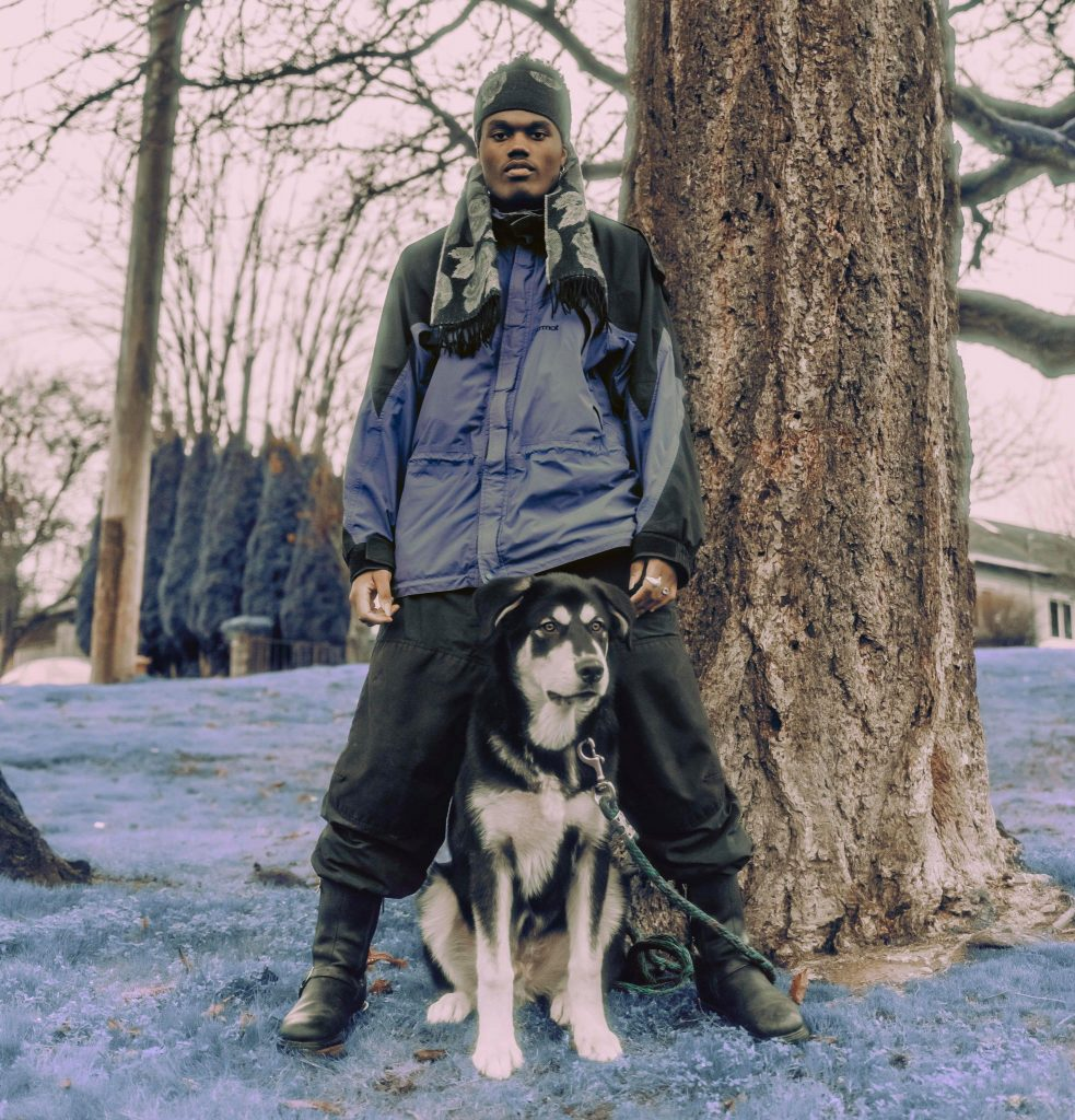 """Topp has a new single """"Glow"""". Here he is pictured dressed in winter wear while holding a dog by the leash outside in a cold looking environment."""