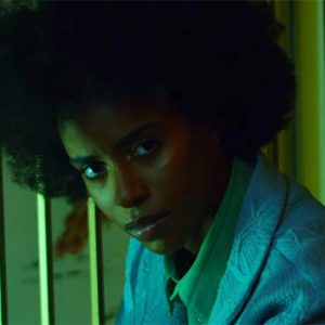 """Angel Haze has a new single called """"Weight"""". Here she wears a light blue robe over a green shirt with her hair out."""