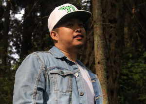 """Patron has a new video called """"F.L.I.P."""". Here he stands in a wooded area with a denim jacket and white and green hat on."""