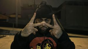 Makkk Hussien wears a black beanie and makes a 'W' with his hands.