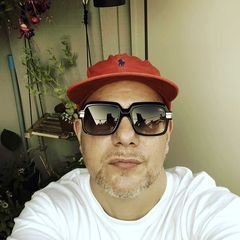 TrussOne wears a red hat, a white t-shirt, and sunglasses.