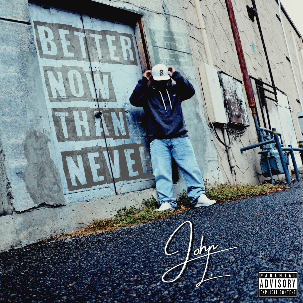 "On cover of John L. ""Better Now Than Never"" album, the rapper/producer is seen standing against a building with a cap pulled down over his face."