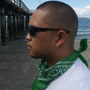 """Patron dropped a video for """"La Familia"""". Here he is wearing black sunglasses and a green bandana while standing under a pier."""
