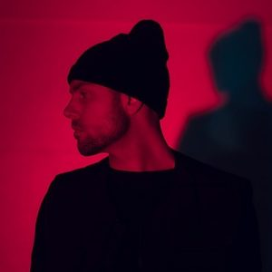 """Sam Shoemaker has a new video for his track """"Freedom"""". Here he is pictured wearing a black beanie with a red tint over the image."""