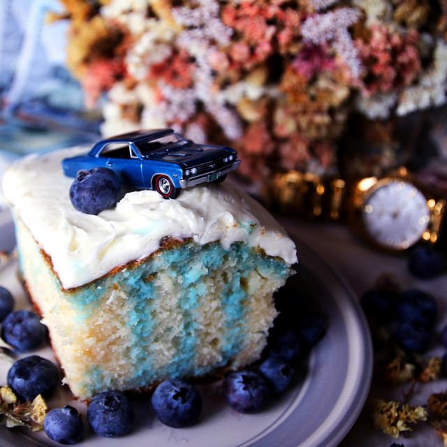 "Blake Anthony has a new single in ""Jello Cake"" and pictured here on the cover is a decadent cake sitting on top of blueberries with a toy blue classic car on top."