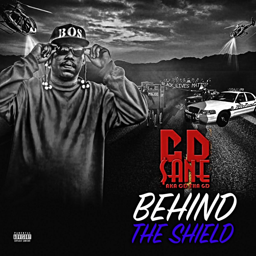 """Cover for CD $ane's """"Behind The Shield"""" shows the rapper putting on black Loc sunglasses while a cop car is parked behind him."""