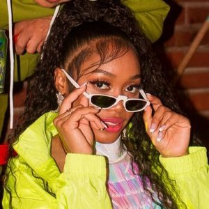 "Chanarah has a new single called ""Glow"" and here she is pictured taking off white sunglasses and wearing a yellow-green jacket."