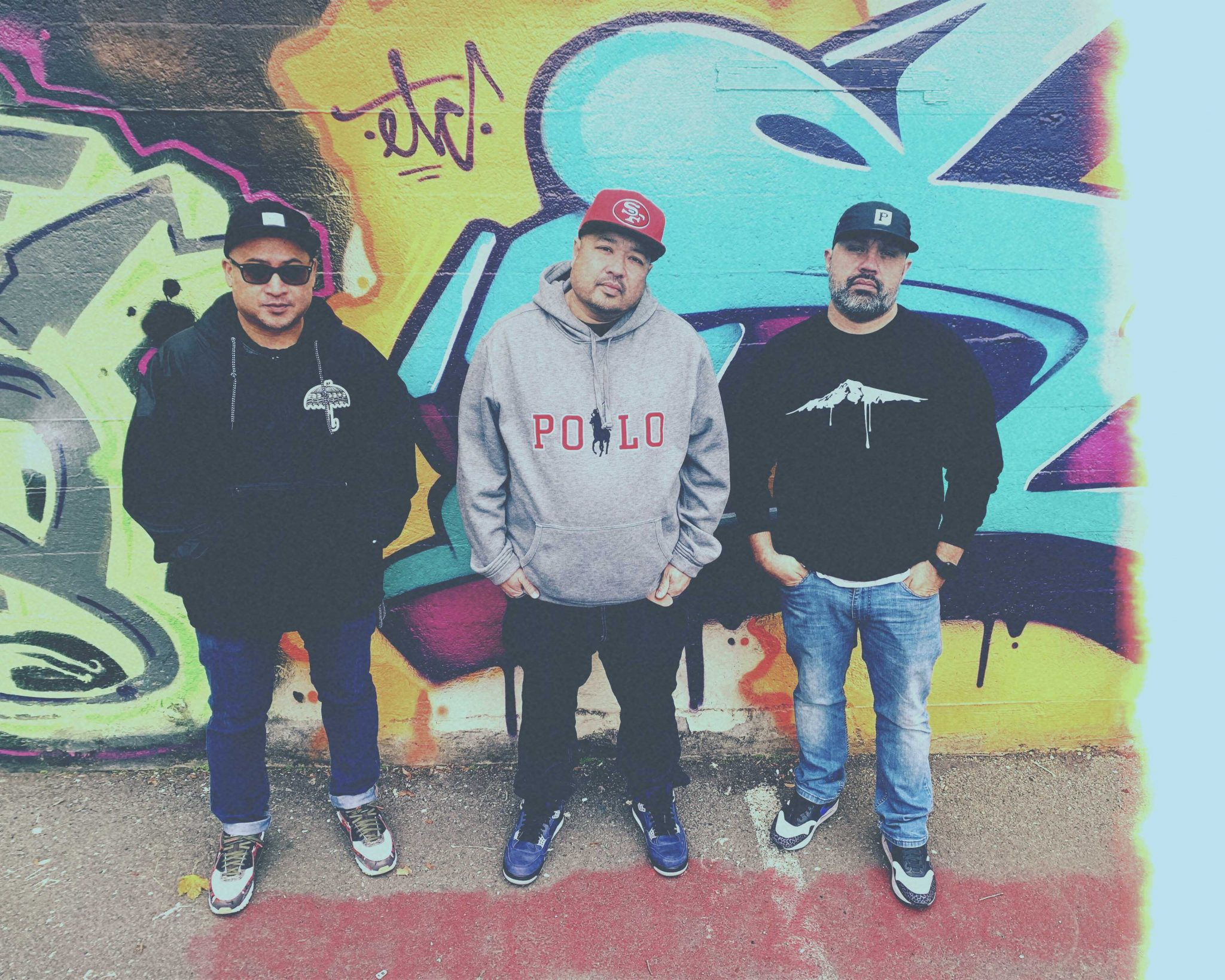 Members of the Boom Bap Project stand in front of a graffiti tagged wall. Check out this interview.