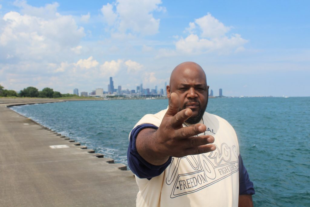 Precise outstretches his arm while standing outside by the edge of Lake Michigan near Chicago.